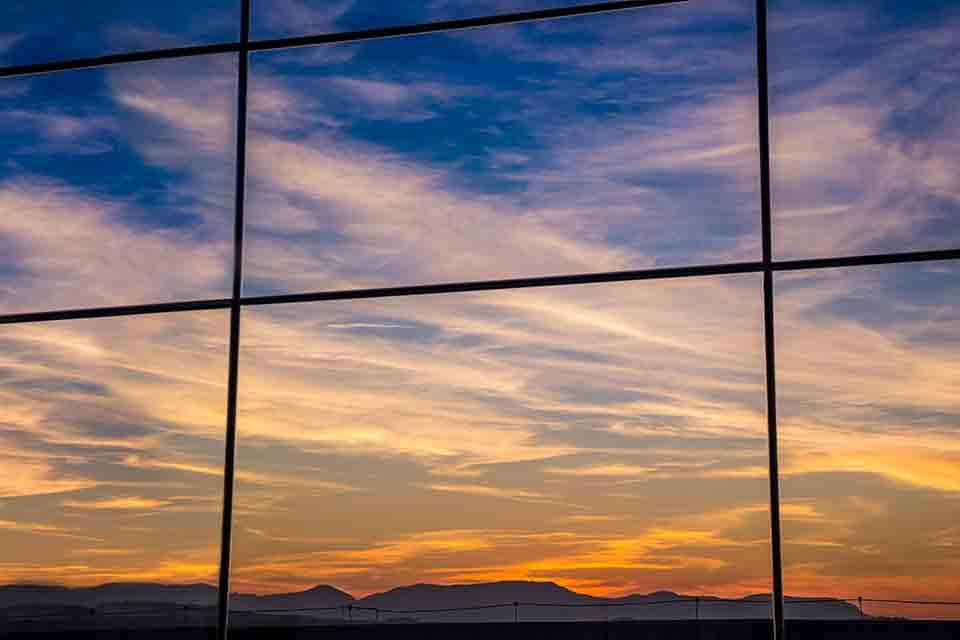Diagramação de livros: a capa da publicação tem a foto do reflexo do pôr do sol no vidro espelhado do Centro de Eventos Faccat
